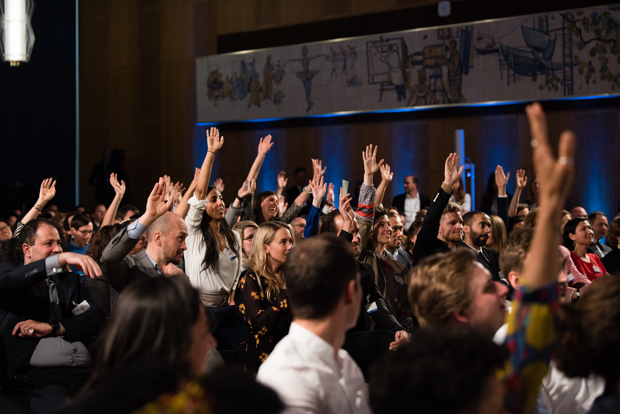People raising their hands at President Barack Obama's town hall event at ESMT Berlin